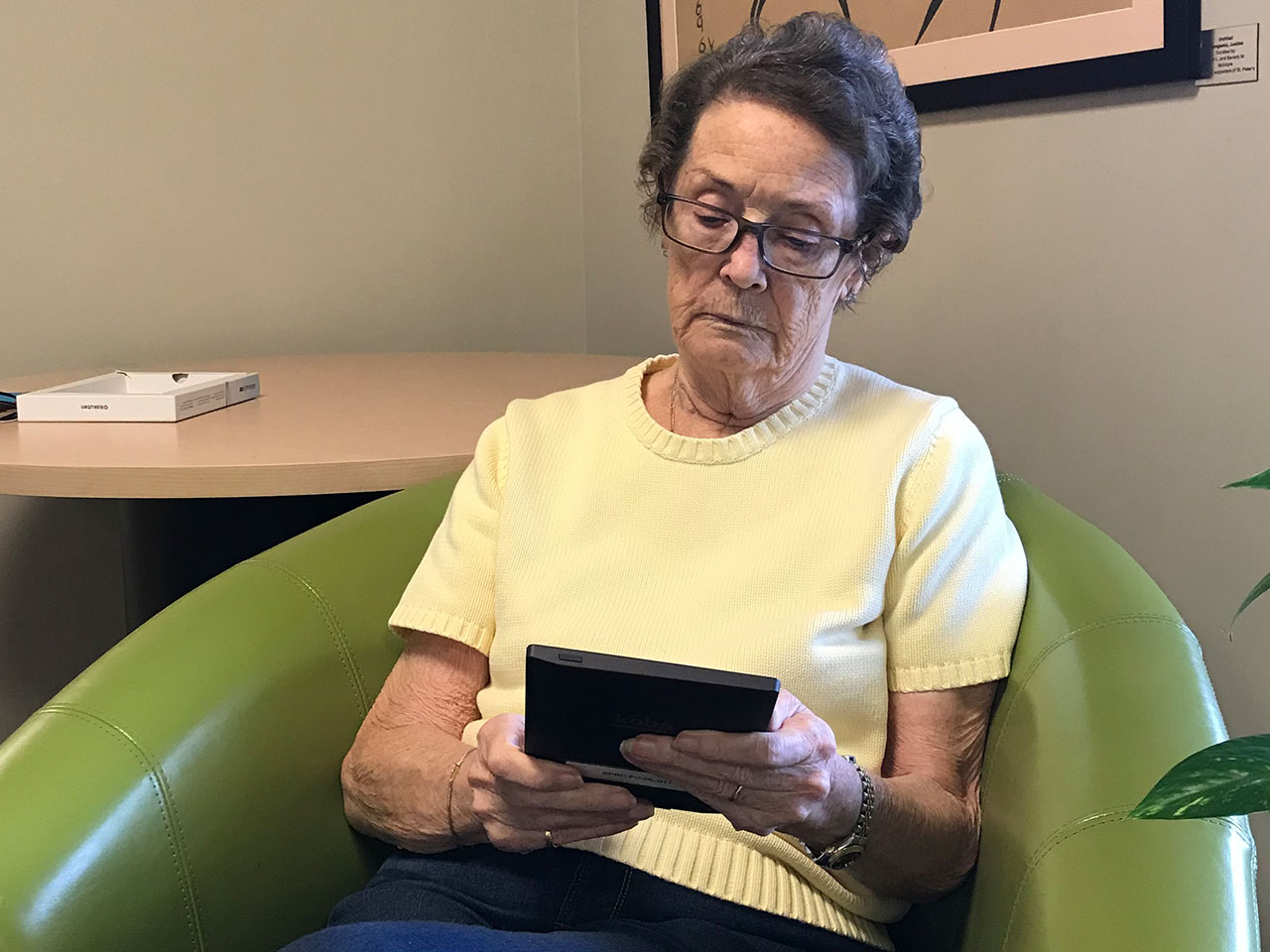 Elderly female resident reading book on electronic reader tablet