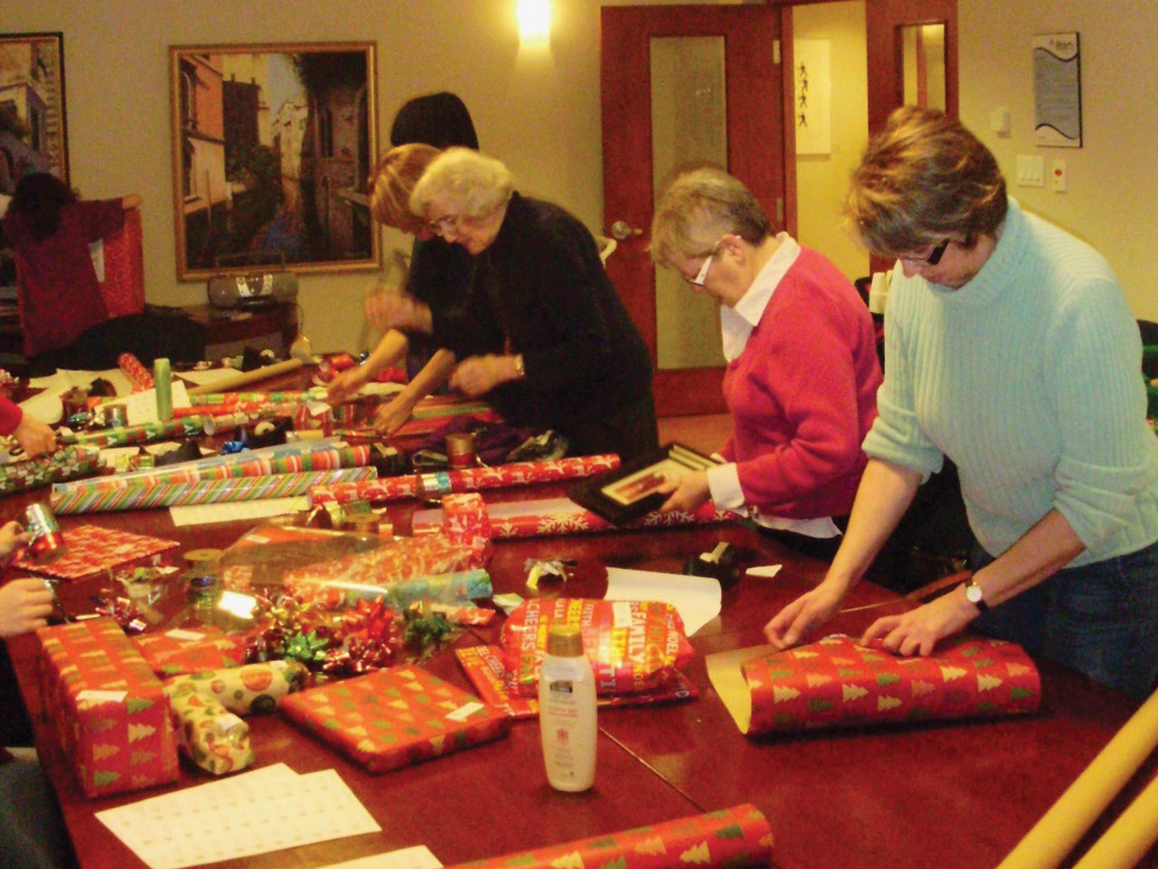 Volunteers wrapping presents on a long table