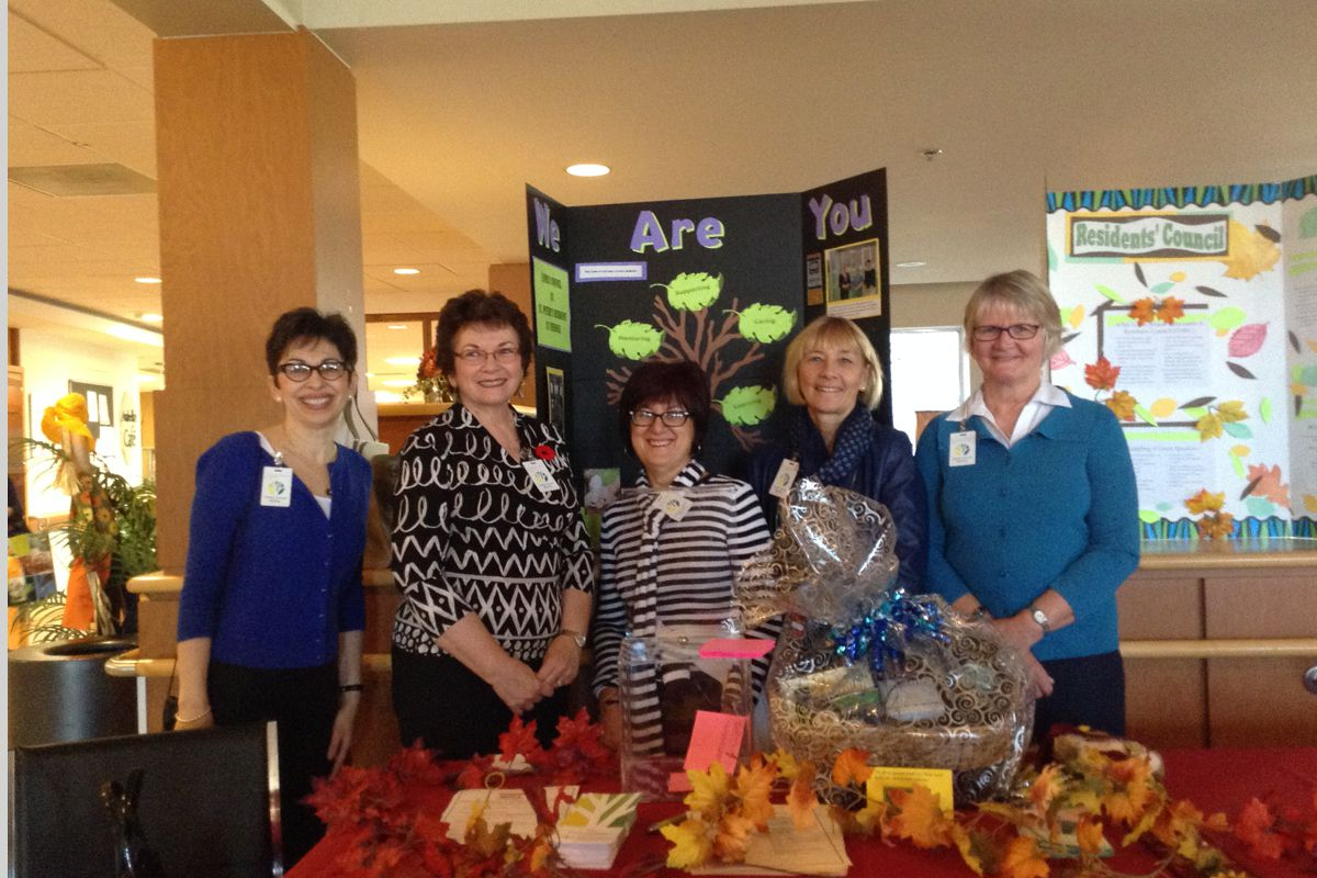 Residents posing with fall table spread