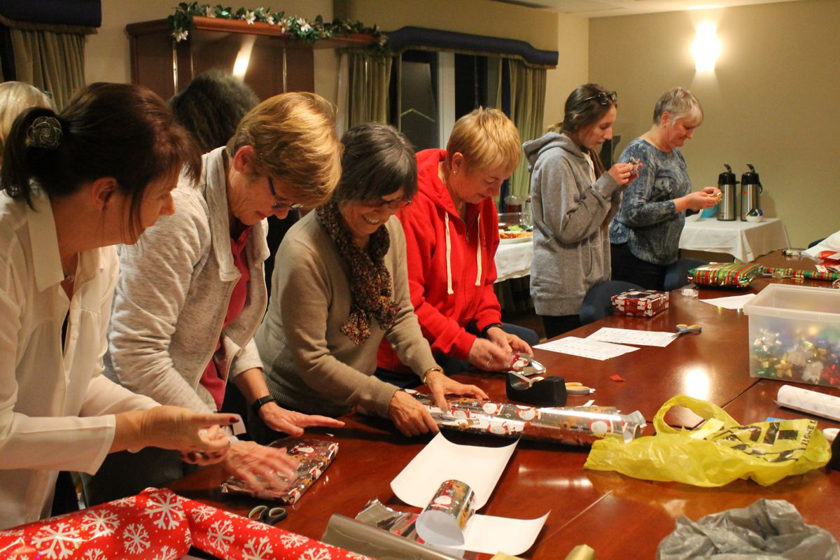 Volunteers enjoying themselves while wrapping presents