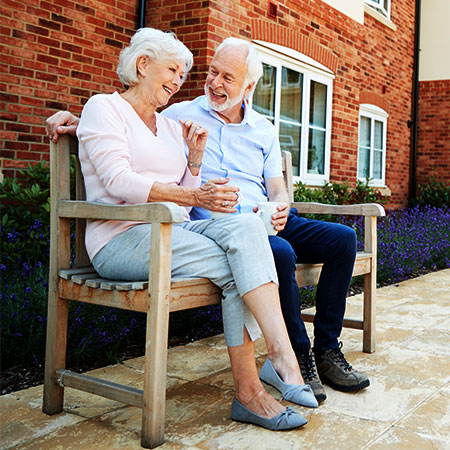 Group of seniors outdoors conversing with care provider