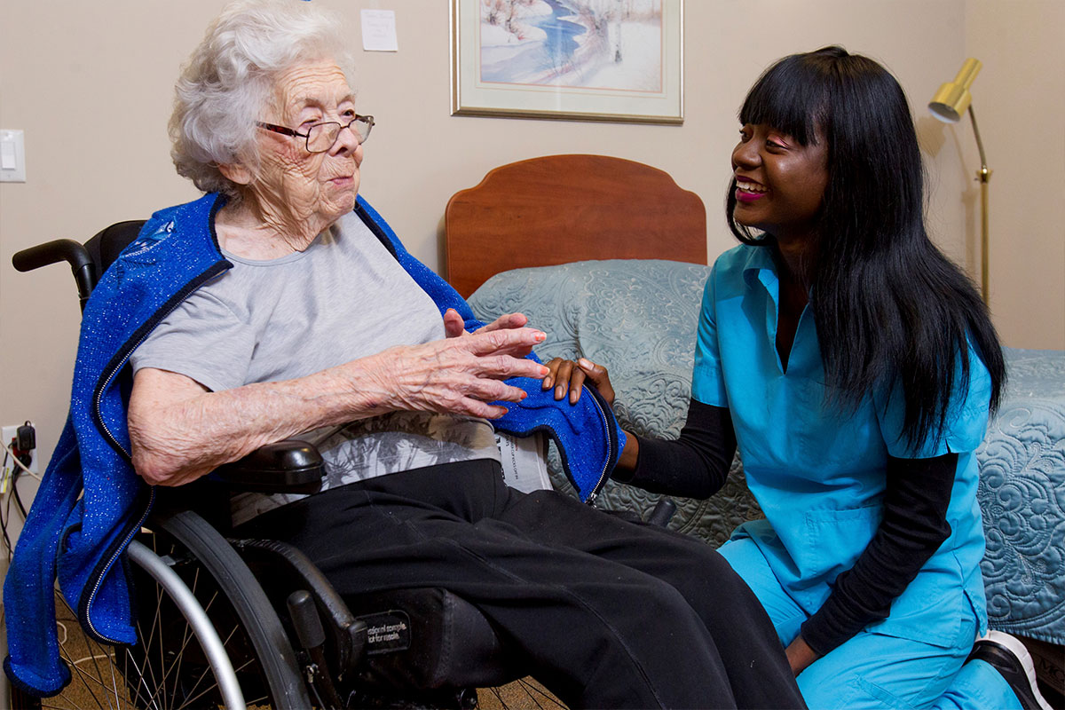 Care provider conversing with elderly resident